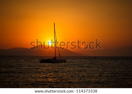 sunset with drifting sail boat
