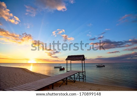 Sunset with jetty silhouette in tropical island  - stock photo