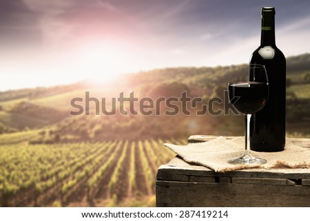 sunset with landscape of tuscany and bottle of red wine