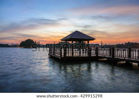 Sunset with low light long exposure scenery of a lake with wooden observation jetty in blue hour, with motion blur effects on surface of water and sky.