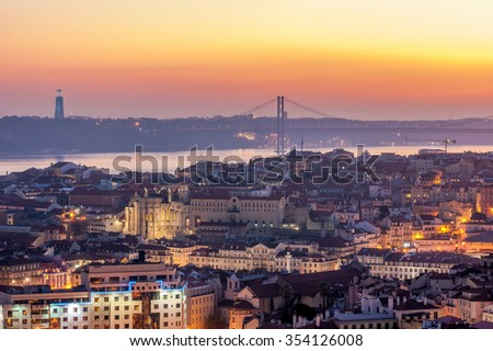 Sunset with orange tones from the Monte Agudo viewpoint in Lisbon, capital of Portugal. In the background the 25th of April Bridge and The Christ the King statue, symbols of the city - stock photo