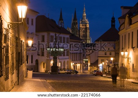 Sunset with Prague castle and lane on Hradcany in Prague at night lighting with shadow of walking couple.