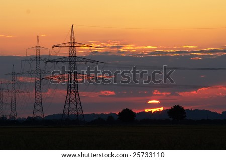 Sunset with pylons supporting transmission high voltage cables - stock photo