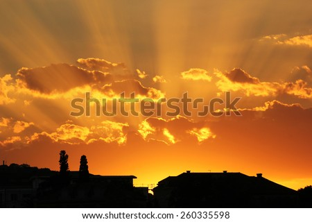 Sunset with rays of sun over the clouds, with silhouettes of the town houses.