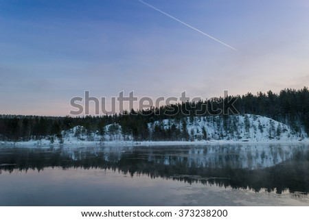 Sunset with reflection of winter forest on the lake and a plane trail in the sky - stock photo