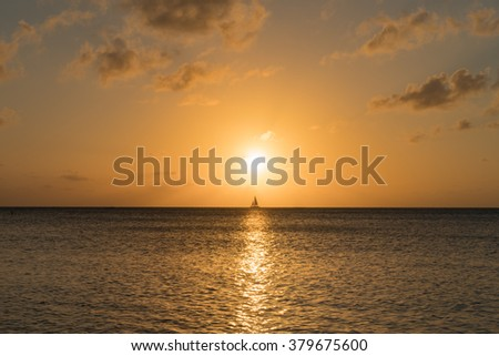 Sunset with Sail Yacht at Seven Mile Beach in Grand Cayman Island - stock photo
