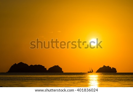 Sunset with sailboat silhouette - stock photo