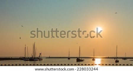 Sunset with sailing boats in the Frisian city of Stavoren, The Netherlands - stock photo