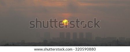 Sunset with smog and dust in the air - stock photo