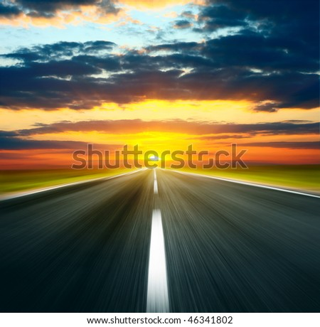 Sunset with sun and clouds over asphalt road