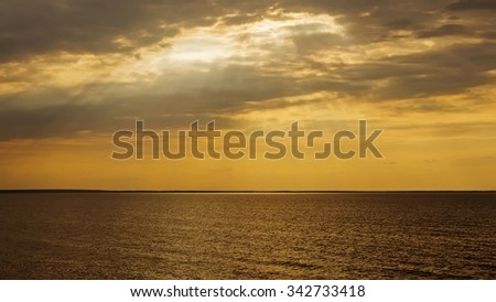 Sunset with sun rays and clouds in the sea - stock photo