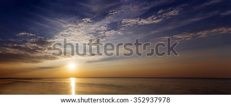 Sunset with sun rays and clouds in the sea panorama