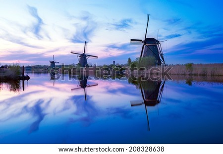 Sunset with the dutch windmills at Kinderdijk in the Netherlands, an UNESCO world heritage site. - stock photo