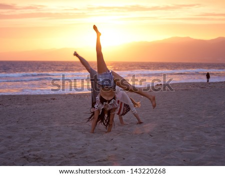 Sunset with Two Beautiful Women doing cartwheels on the Beach in Santa Monica California - stock photo