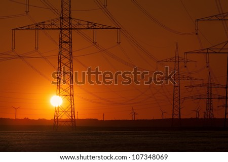 Sunset with Wind Turbines behind Power Lines and a group of Power Towers