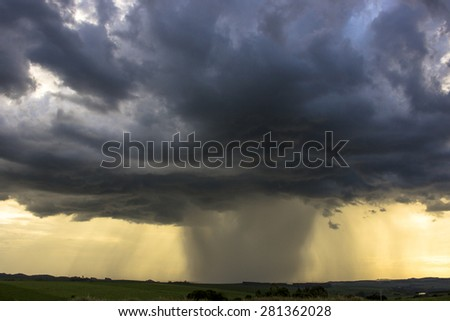 sunset with yellow and blue sky and rain clouds