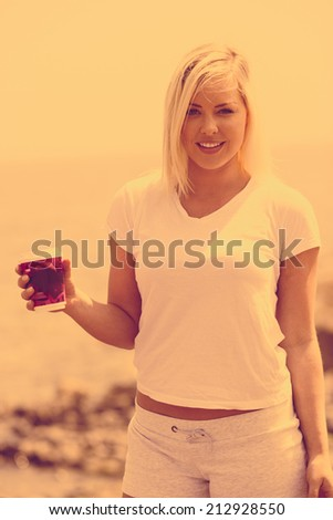 Sunset with young woman with fresh cup of coffee on the beach - stock photo