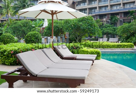 sunshade and chaise longue at the poolside.