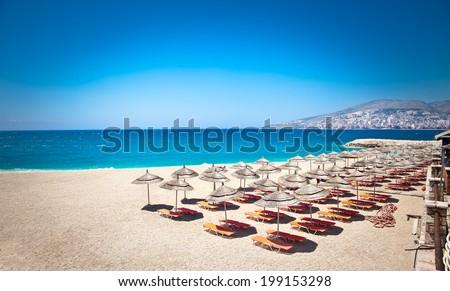 Sunshade umbrellas and deckchairs on the beautiful  Mango beach in Saranda, Albania. - stock photo