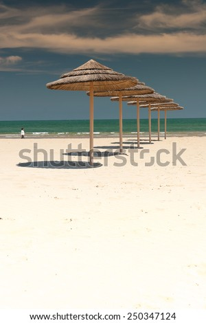 Sunshade Umbrellas on the beach at summer day - stock photo