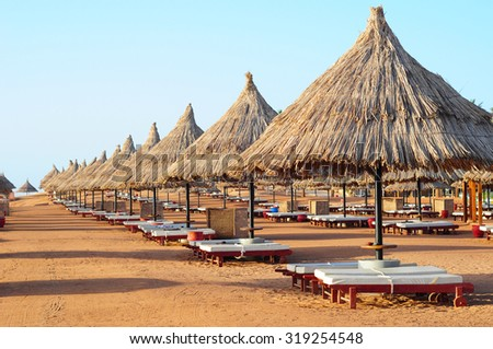 Sunshade umbrellas on the beach with green coconut palms straw sunshades and wooden sunbeds in front of a turquoise sea with a blue sky. - stock photo