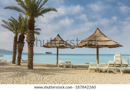 Sunshades and relaxing facilities on the golden beach of Eilat - famous resort city in Israel
