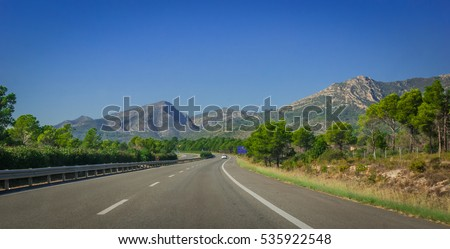 Sunshine on Coastal highway of Spain.  Lone white car drives along through foothills and mountain ranges near the edges of continental Europe, Spain.