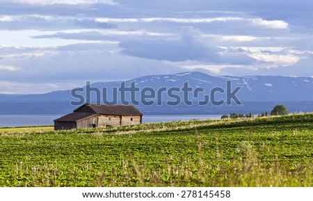 Sunshine over a barn on farmland area. Lake and mountains in shadows in the background. Cloudy sky, snow on the mountain. Great-Lake area, Sweden. - stock photo