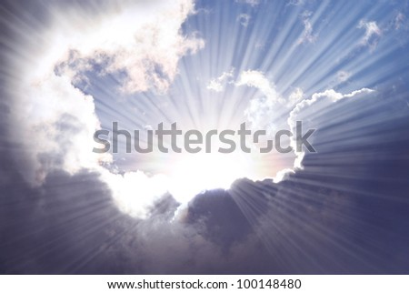Sunshine rays among dramatic clouds. - stock photo