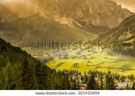 Sunshine to alpine village in Corvara, Dolomites, Italy  - stock photo
