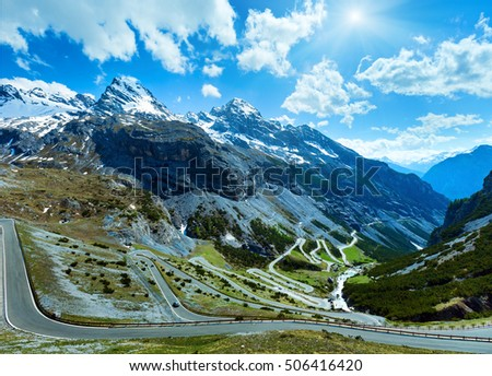 Sunshiny summer Stelvio pass with alpine road and snow on slope (Italy)