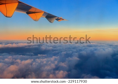 Sunsrise over a clouds. View from aircraft window with paint effect - stock photo