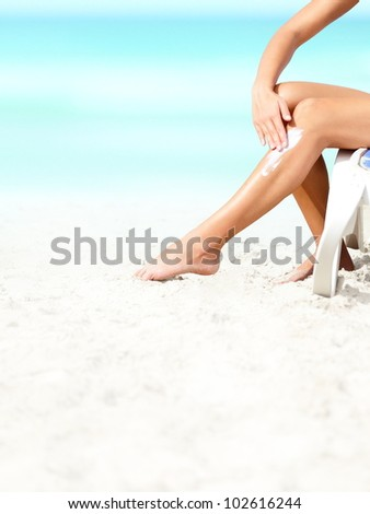 Suntan lotion / sunscreen. Woman applying sunblock cream on leg on beautiful tropical beach with white sand on summer vacation.