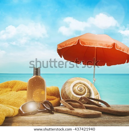 Suntan lotion with towel and sandals at the beach - stock photo