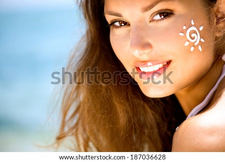 Suntan Lotion Woman Applying Sunscreen Solar Cream. Beautiful happy cute Girl applying Sun Tan Cream on her Face over ocean background. Sun Tanning. Skin care and Protection. Vacation - stock photo