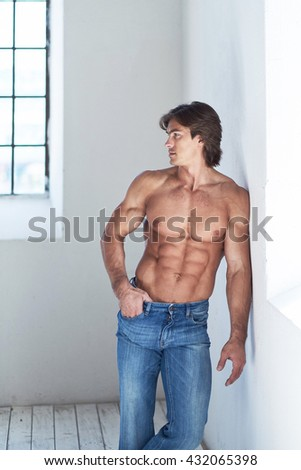 Suntanned muscular male in blue jeans posing in natural light from window.