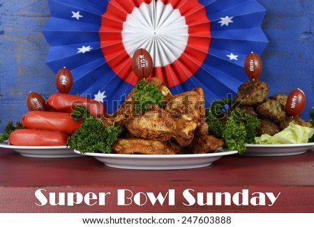 Super Bowl Sunday football party celebration food plates with chicken buffalo wings, meat balls, hot dogs and USA party decorations, with text. - stock photo