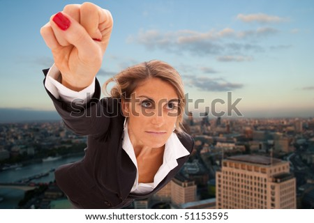 Super businesswoman flying over London city - stock photo