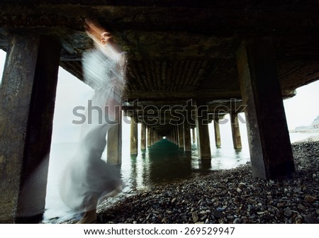 Super cute bride at storm under dark sea pier