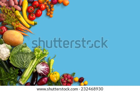 Super food background / studio photo of different fruits and vegetables on blue backdrop  - stock photo