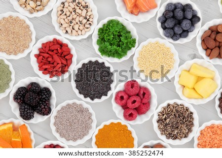 Super food collection in porcelain crinkle bowls over distressed wooden background. High in vitamins and antioxidants. - stock photo