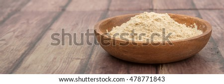 Super food maca powder in wooden bowl over wooden background
