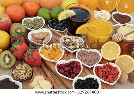 Super food selection for cold and flu remedy including foods high in vitamin c and antioxidants with herbal medicine and supplement capsules. - stock photo