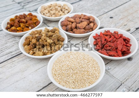 Super food tiger nuts, mulberry berries, cacao beans, goji berries, quinoa seeds, golden berry in white bowls over wooden background.