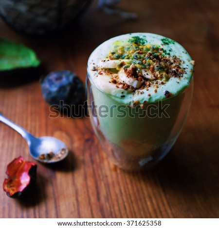 Super green smoothie;  Avocado, banana, celery, cucumber and matcha green tea greek yogourt smoothie layered on chia seeds pudding topping with passion fruit and crushed grilled almond. - stock photo