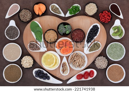 Super health food selection in bowls on a heart shaped board over lokta paper background. - stock photo