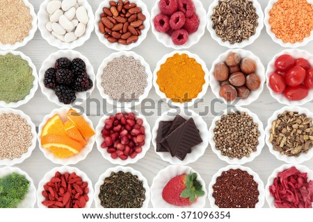 Super health food selection in porcelain crinkle bowls over distressed wooden background. High in vitamins and antioxidants. - stock photo