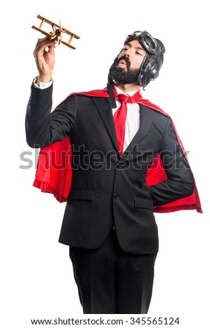 Super hero businessman holding a wooden toy airplane