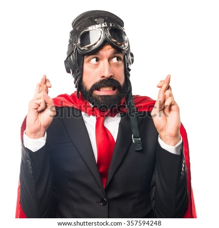 Super hero businessman with his fingers crossing - stock photo