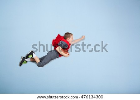 Super hero football kid wearing a cape and flying through the air